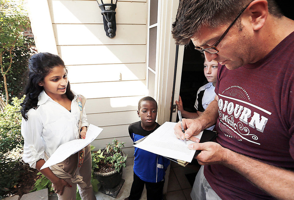 Photo - Tanvi Saran, 13, watches as neighbor Andy McDonald signs her petition as she works on her Silver Award Girl Scout project on Friday.  Beside McDonald are his sons Bo, 8, and Jacin, 11.  Photo by Steve Sisney, The Oklahoman  STEVE SISNEY - THE OKLAHOMAN