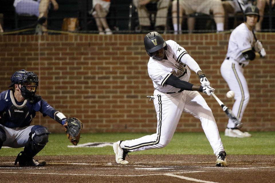 Photo - Vanderbilt's Xavier Turner doubles and drives in a run against Xavier in the bottom of the fourth inning in an NCAA college baseball tournament regional game Friday, May 30, 2014, in Nashville, Tenn. Catching for Xavier is Daniel Rizzie. (AP Photo/Mark Humphrey)
