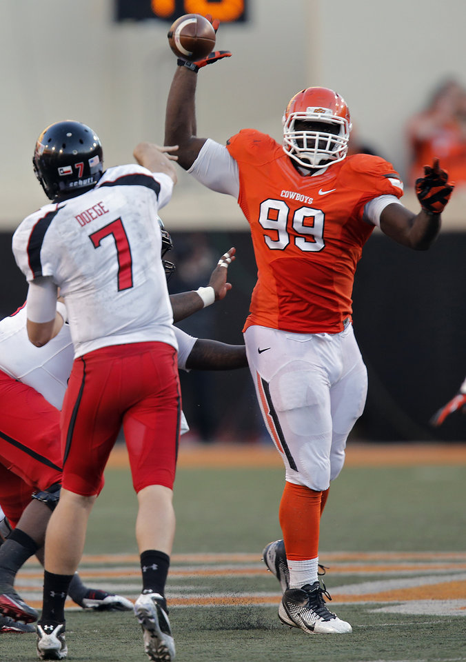Photo - Oklahoma State's Calvin Barnett (99) tries to block a pass by Texas Tech's Seth Doege (7) during the college football game between the Oklahoma State University Cowboys (OSU) and Texas Tech University Red Raiders (TTU) at Boone Pickens Stadium on Saturday, Nov. 17, 2012, in Stillwater, Okla.   Photo by Chris Landsberger, The Oklahoman