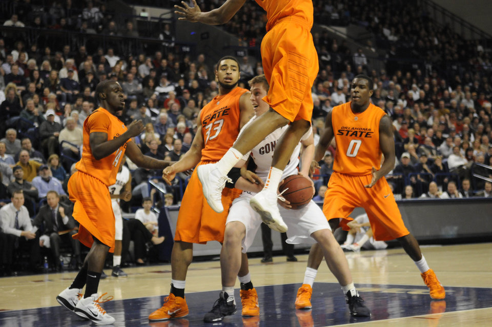 Photo - Gonzaga's Kelly Olynk (13) drives through Oklahoma State's defence, from left, Ray Penn (14), Marshall Moses (33) and Jean-Paul Olukemi (0) in the second half of an NCAA college basketball game, Friday, Dec. 31, 2010, in Spokane, Wash. Gonzaga beat Oklahoma State 73-52. (AP Photo/Jed Conklin)