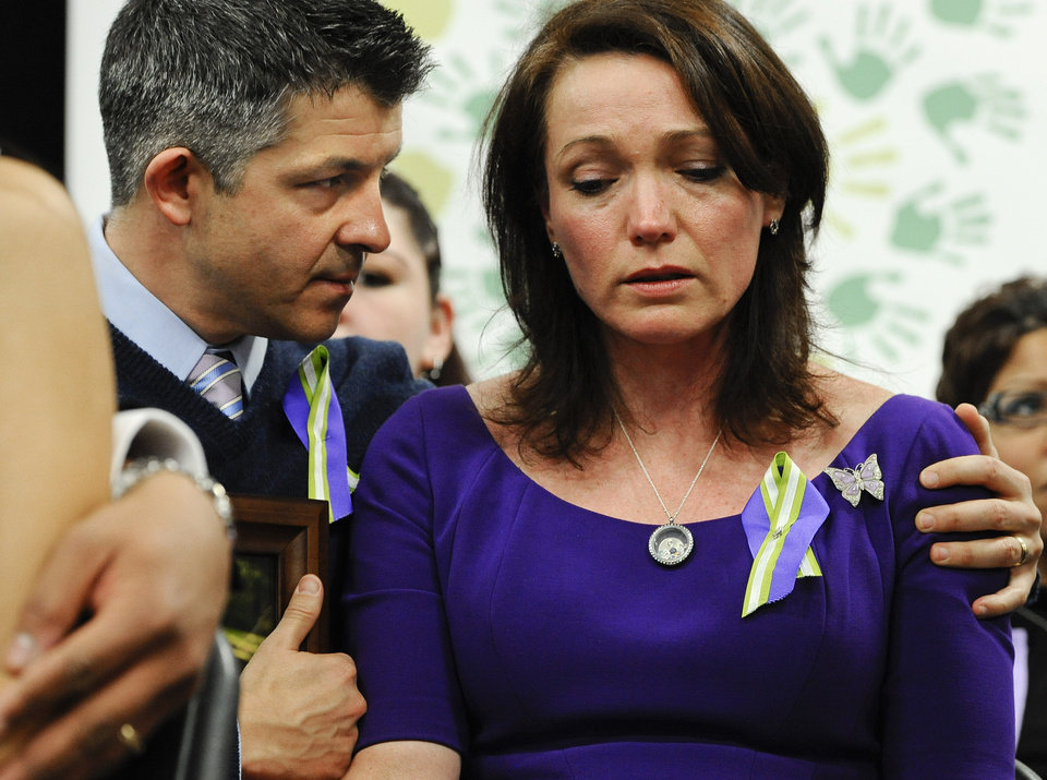 Photo - Ian and Nicole Hockley, parents of Sandy Hook School shooting victim Dylan, listen at a news conference at Edmond Town Hall in Newtown, Conn., Monday, Jan. 14, 2013. One month after the mass school shooting at Sandy Hook Elementary School, the parents joined a grassroots initiative called Sandy Hook Promise to support solutions for a safer community. (AP Photo/Jessica Hill)