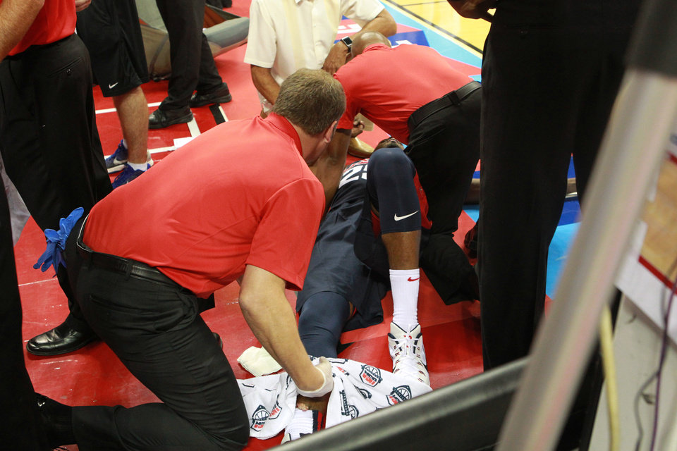 Photo - Indiana Pacers' Paul George is attended to after injuring his right leg during the USA Basketball Showcase Friday, Aug. 1, 2014, in Las Vegas. (AP Photo/Las Vegas Sun, Sam Morris)