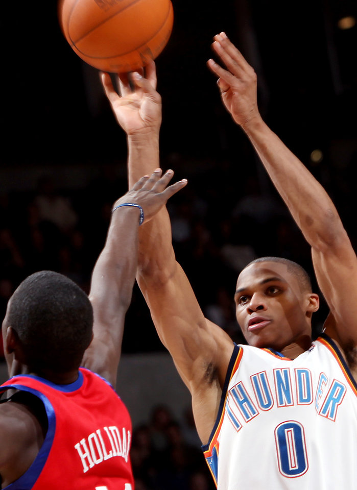 Photo - Oklahoma City's Russell Westbrook puts up a shot in front of Philadelphia's Jrue Holiday during the second half of their NBA basketball game at the Ford Center in Oklahoma City on Wednesday, Dec. 2, 2009. The Thunder beat the 76ers 117 to 106. By John Clanton, The Oklahoman ORG XMIT: KOD