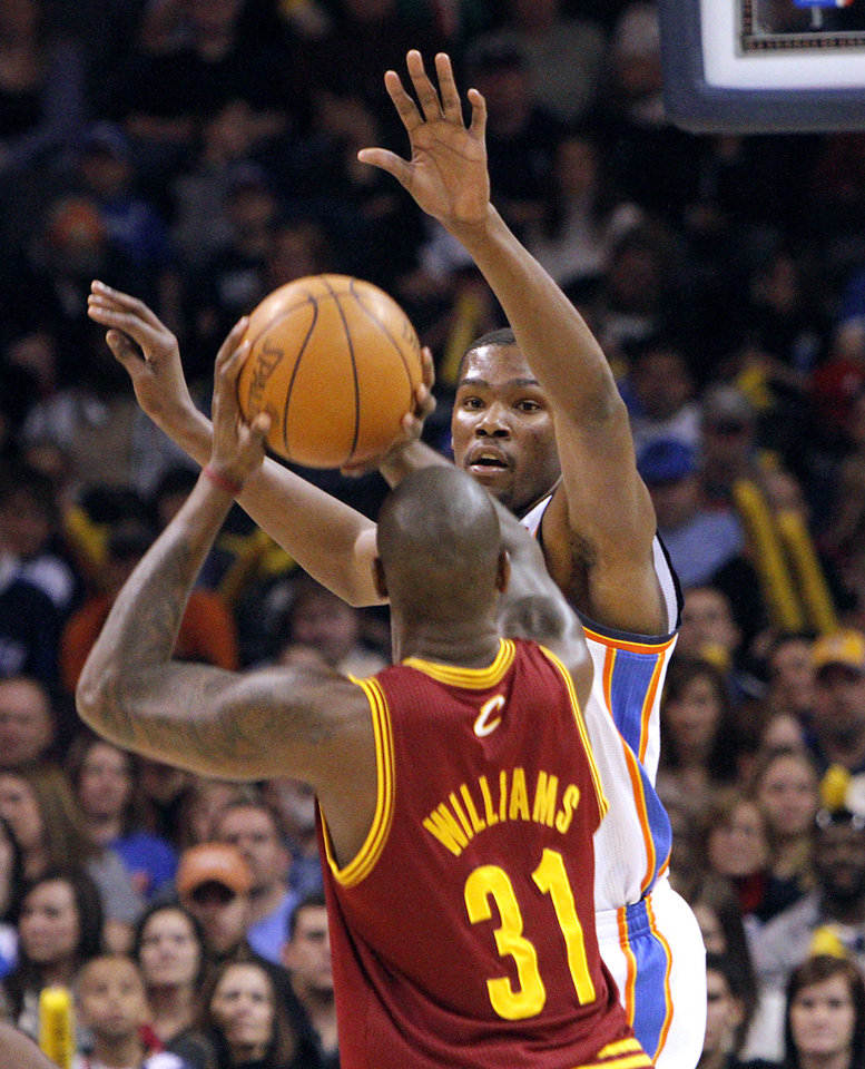 Photo - Oklahoma City's Kevin Durant pressures a shot by Cleveland's Jawad Williams during the first half of their NBA basketball game at the OKC Arena in Oklahoma City on Sunday, Dec. 12, 2010.  The Thunder beat the Cavaliers106-77. Photo by John Clanton, The Oklahoman