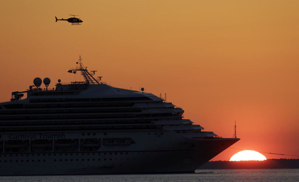 Photo - The cruise ship Carnival Triumph is towed into Mobile Bay near Dauphin Island, Ala., Thursday, Feb. 14, 2013. The ship with more than 4,200 passengers and crew members has been idled for nearly a week in the Gulf of Mexico following an engine room fire. (AP Photo/Dave Martin)