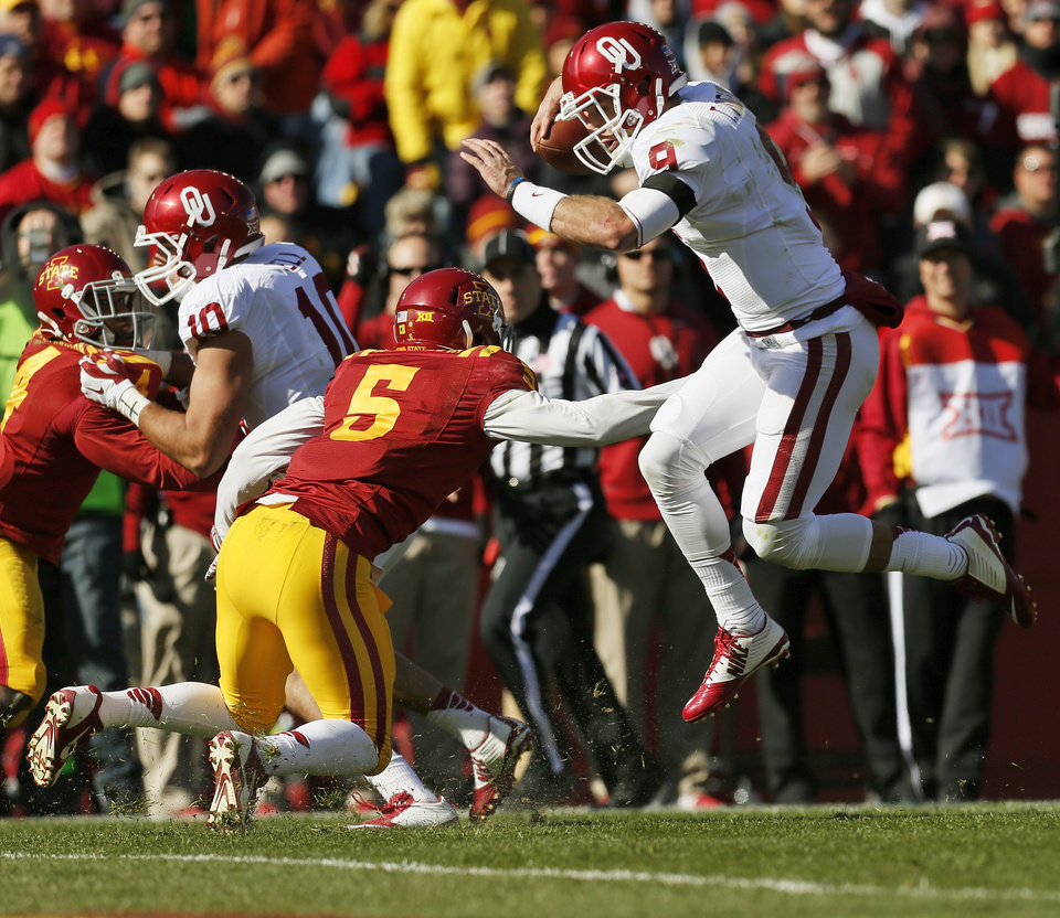 Photo - Oklahoma's Trevor Knight (9) leaps to get past Iowa State's Kamari Cotton-Moya (5) as he rushes for a touchdown in the second quarter during a college football game between the University of Oklahoma Sooners (OU) and the Iowa State Cyclones (ISU) at Jack Trice Stadium in Ames, Iowa, Saturday, Nov. 1, 2014. Photo by Nate Billings, The Oklahoman