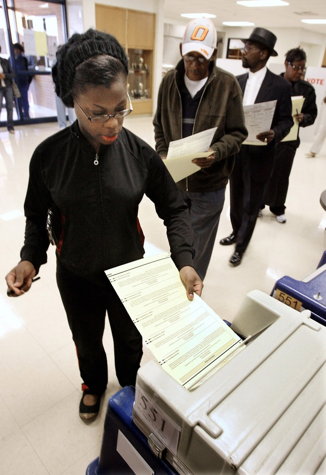 Photo - Chasity Dozier, Okla. City, places her ballot in the voting machine at precinct 551, Millwood High School, in Oklahoma City Tuesday, Nov. 4, 2008.  BY PAUL B. SOUTHERLAND, THE OKLAHOMAN