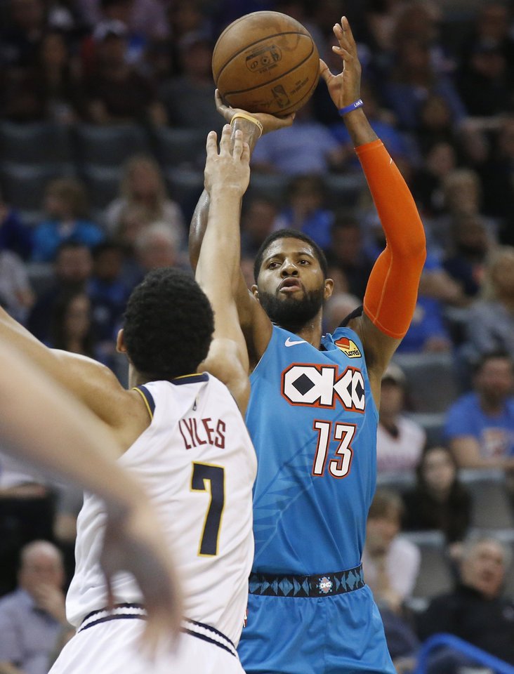 Photo - Oklahoma City Thunder forward Paul George (13) shoots as Denver Nuggets forward Trey Lyles (7) defends in the second half of an NBA basketball game Friday, March 29, 2019, in Oklahoma City. (AP Photo/Sue Ogrocki)