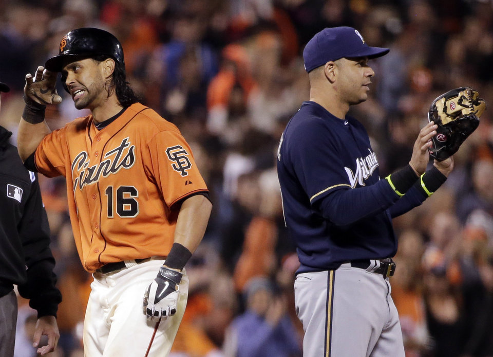 Photo - San Francisco Giants' Angel Pagan salutes toward his dugout after a stand-up triple, next to Milwaukee Brewers third baseman Aramis Ramirez during the fifth inning of a baseball game Friday, Aug. 29, 2014, in San Francisco. (AP Photo/Marcio Jose Sanchez)