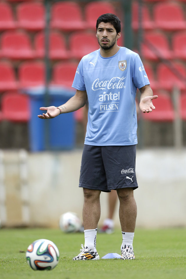 Photo - Luis Suarez joins his team's practice session at Arena do Jacare Stadium before the start of the World Cup soccer tournament in Sete Lagoas, Brazil, Thursday, June 12, 2014.  (AP Photo/Bruno Magalhaes)