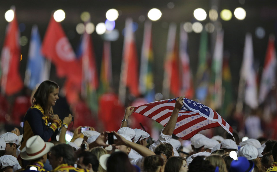 Photo -   An athlete holds the U.S. flag as he enters the stadium with others during the Closing Ceremony at the 2012 Summer Olympics, Sunday, Aug. 12, 2012, in London. (AP Photo/Matt Slocum)