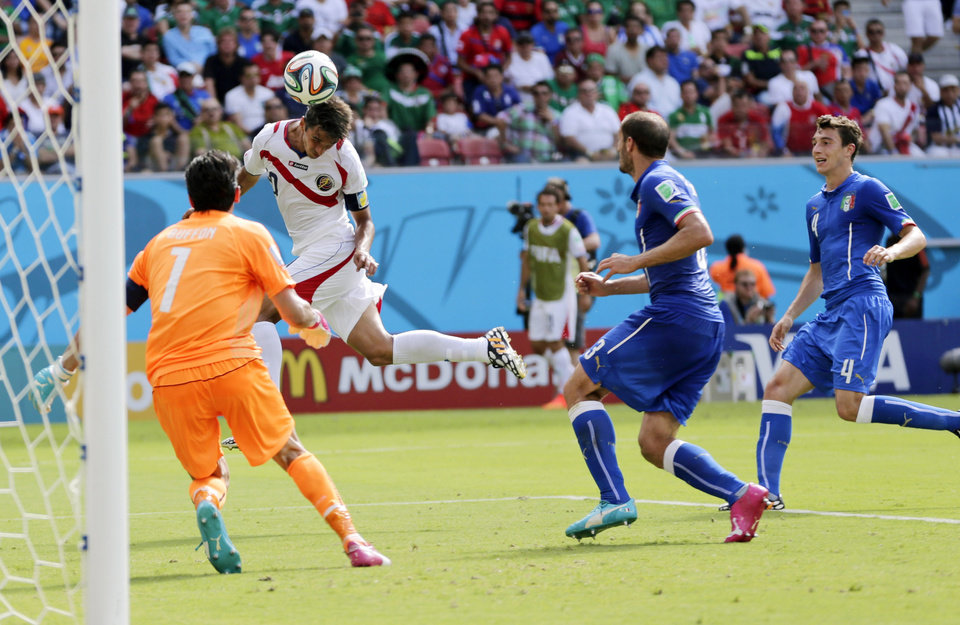 Photo - Costa Rica's Bryan Ruiz heads the ball to score his side's first goal over Italy's goalkeeper Gianluigi Buffon during the group D World Cup soccer match between Italy and Costa Rica at the Arena Pernambuco in Recife, Brazil, Friday, June 20, 2014.(AP Photo/Petr David Josek)