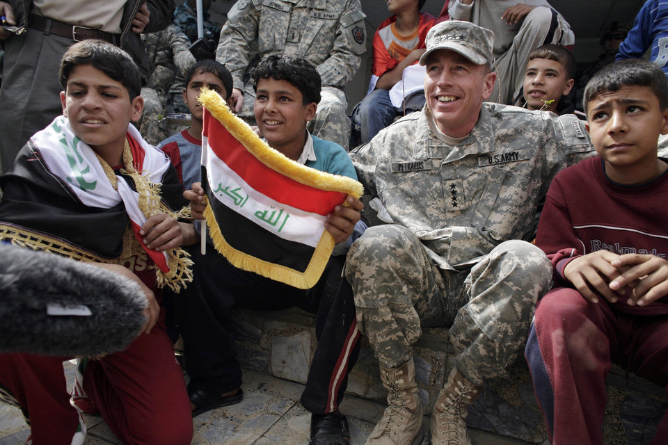 FILE - In this March 1, 2008 file photo, then-top U.S. commander in Iraq, Gen. David Petraeus, sits with Iraqi children during a youth soccer tournament in central Baghdad, Iraq. Gen. Petraeus, the retired four-star general who led the U.S. military campaigns in Iraq and Afghanistan, resigned Friday, Nov. 9, 2012 as director of the CIA after admitting he had an extramarital affair. (AP Photo/Dusan Vranic, File)