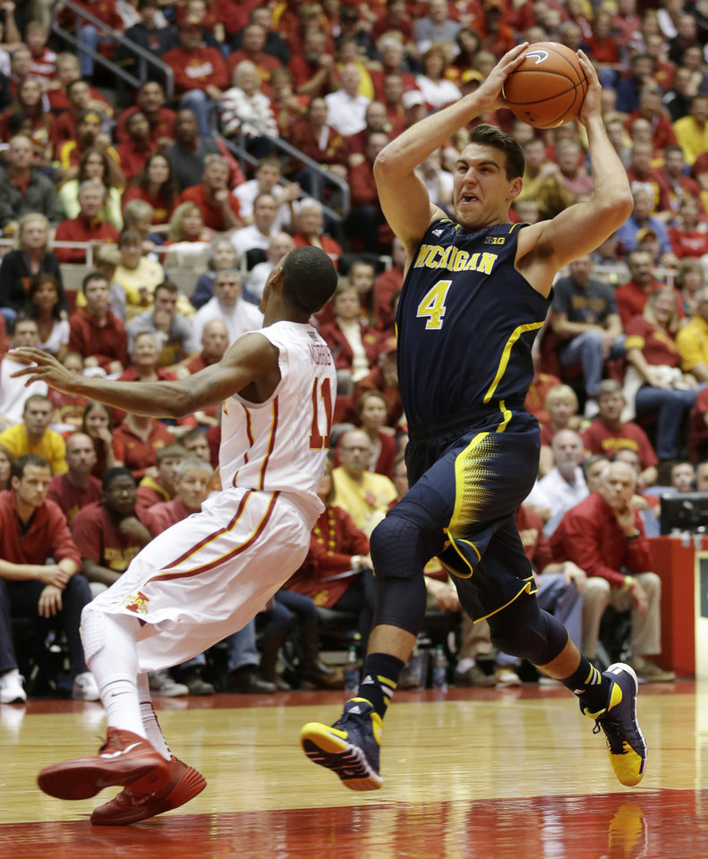 Photo - Michigan forward Mitch McGary drives to the basket past Iowa State guard Monte Morris, left, during the first half of an NCAA college basketball game on Sunday, Nov. 17, 2013, in Ames, Iowa. (AP Photo/Charlie Neibergall)
