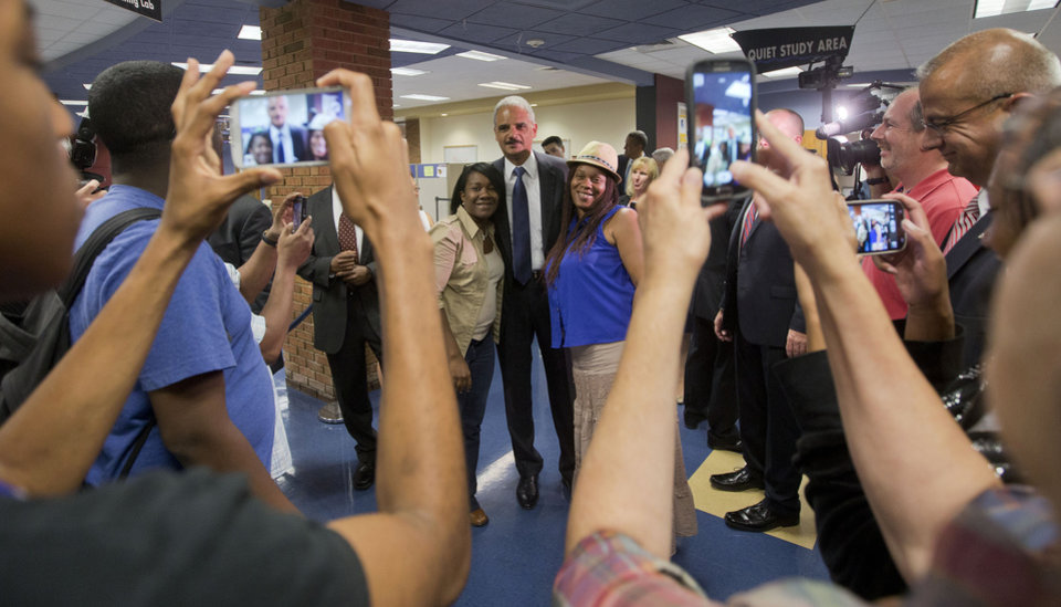Photo - Attorney General Eric Holder, center, poses for photographs following his meeting with students at St. Louis Community College Florissant Valley in Ferguson, Mo., Wednesday, Aug. 20, 2014. Holder arrived in Missouri on Wednesday, a small group of protesters gathered outside the building where a grand jury could begin hearing evidence to determine whether a Ferguson police officer who shot 18-year-old Michael Brown should be charged in his death.  (AP Photo/Pablo Martinez Monsivais, Pool)