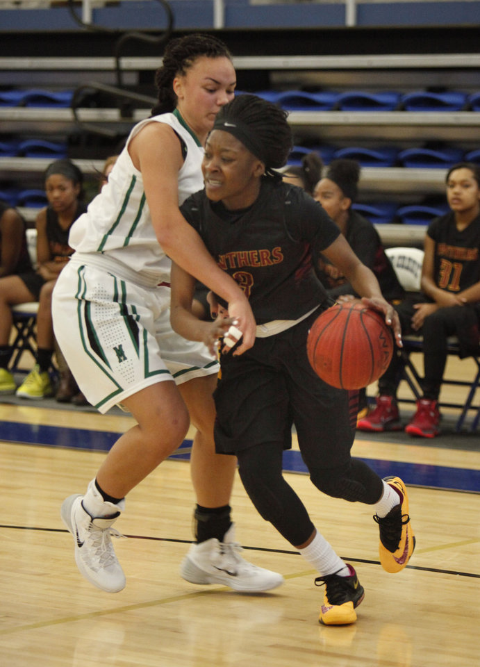 Photo - PC North's Nakylia Carter drives past Bishop McGuinness' Hattie Msuya during the Bishop McGuinness vs. PC North girls game of the Deer Creek, Bruce Gray Invitational basketball game at Deer Creek High School in Oklahoma City, OK, Thursday, January 23, 2014,  Photo by Paul Hellstern, The Oklahoman