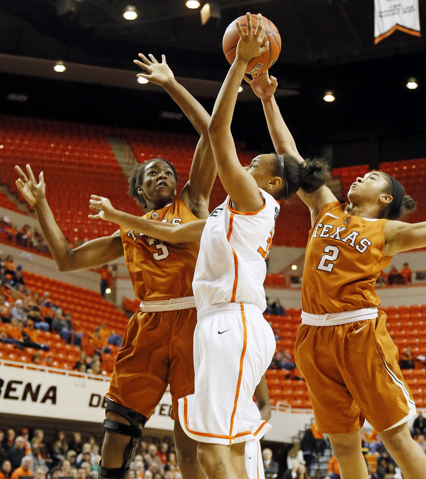 Photo - Oklahoma State's Kendra Suttles (31) takes a shot between Texas' Nneka Enemkpali (3) and Texas' Celina Rodrigo (2) during a women's college basketball game between Oklahoma State University (OSU) and the University of Texas at Gallagher-Iba Arena in Stillwater, Okla., Saturday, March 2, 2013. Photo by Nate Billings, The Oklahoman