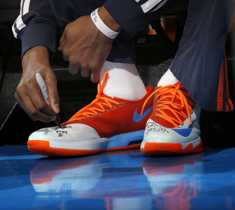Photo - Oklahoma City 's Kevin Durant (35) writes on his shoes before the Game 1 in the first round of the NBA playoffs between the Oklahoma City Thunder and the Memphis Grizzlies at Chesapeake Energy Arena in Oklahoma City, Saturday, April 19, 2014. Photo by Sarah Phipps, The Oklahoman