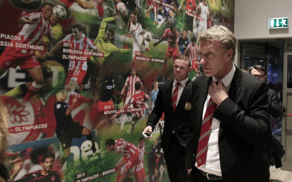 Photo - Manchester United's coach David Moyes, right, and player Wayne Rooney arrive for a news conference at Georgios Karaiskakis stadium, in Piraeus port, near Athens, on Monday, Feb. 24, 2014. Manchester United will play against Olympiakos in the Champions League's round of 16 on Tuesday. (AP Photo/Thanassis Stavrakis)