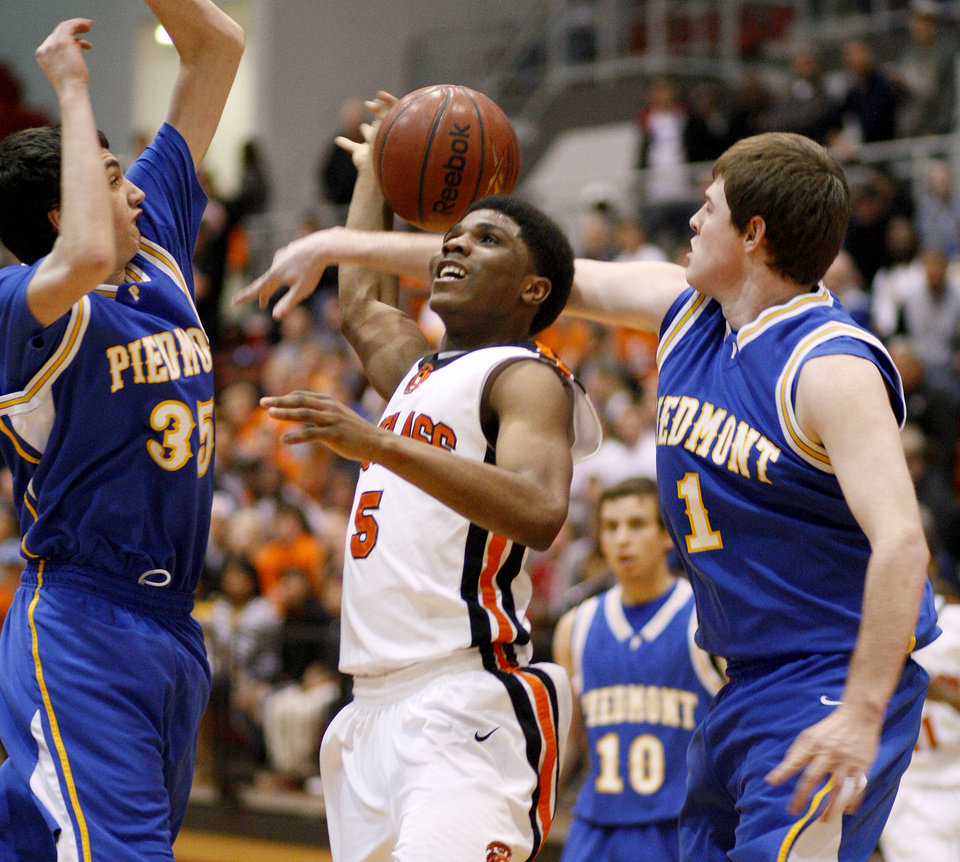 Stephen Clark of Douglass is fouled as he goes between Piedmont's Connor McFall, at right, and Grant Gipson during a Class 4a boys basketball state tournament game in Midwest CIty, Okla., Thursday, March 8, 2012. Photo by Bryan Terry, The Oklahoman