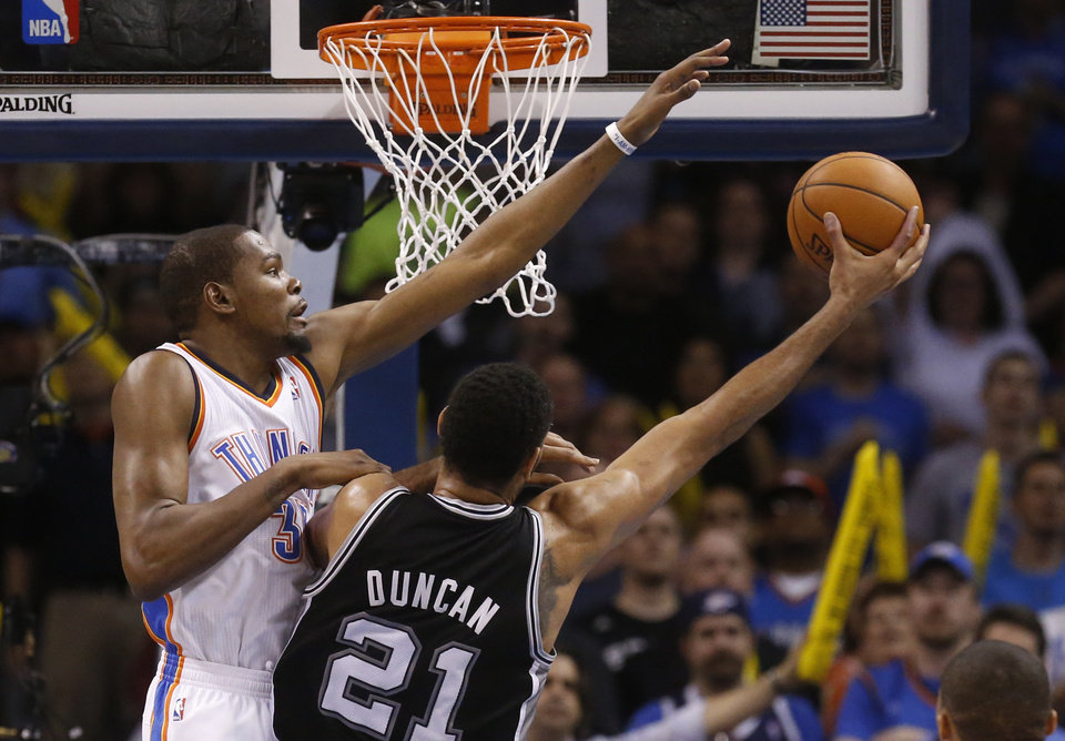 Photo - Oklahoma City Thunder forward Kevin Durant (35) attempts to block a shot by San Antonio Spurs forward Tim Duncan (21) in the second quarter of an NBA basketball game in Oklahoma City, Thursday, April 3, 2014. (AP Photo/Sue Ogrocki)