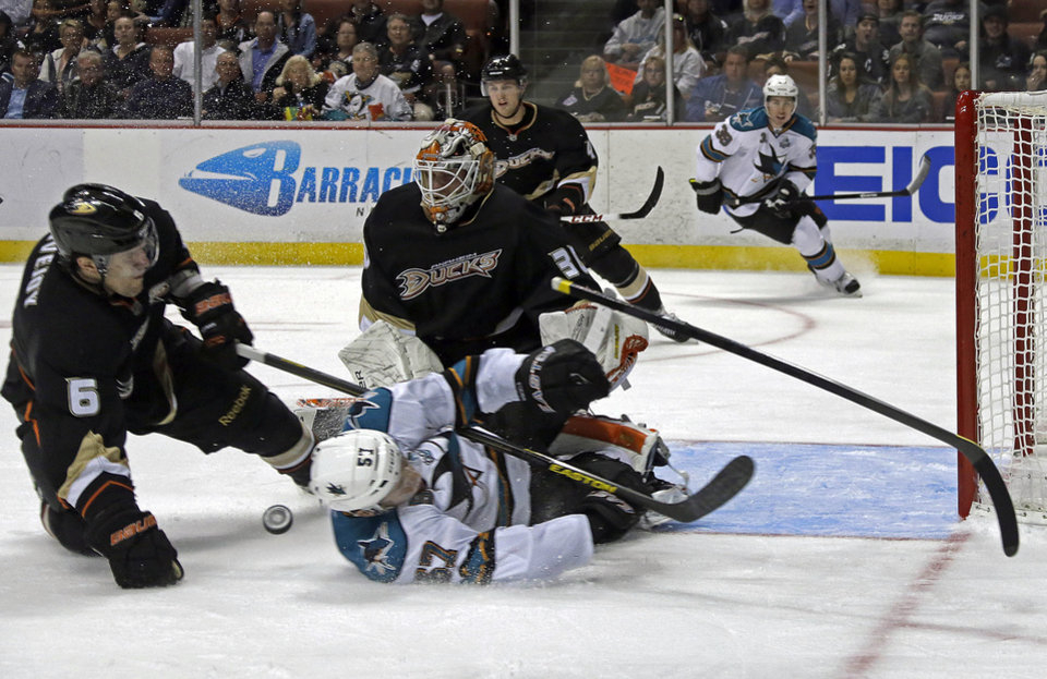 Photo - Anaheim Ducks defenseman Ben Lovejoy (6) is charged with hooking as he tangles with San Jose Sharks center Tommy Wingels (57) in the first period of an NHL hockey game in Anaheim, Calif., Monday, March 25, 2013. (AP Photo/Reed Saxon)