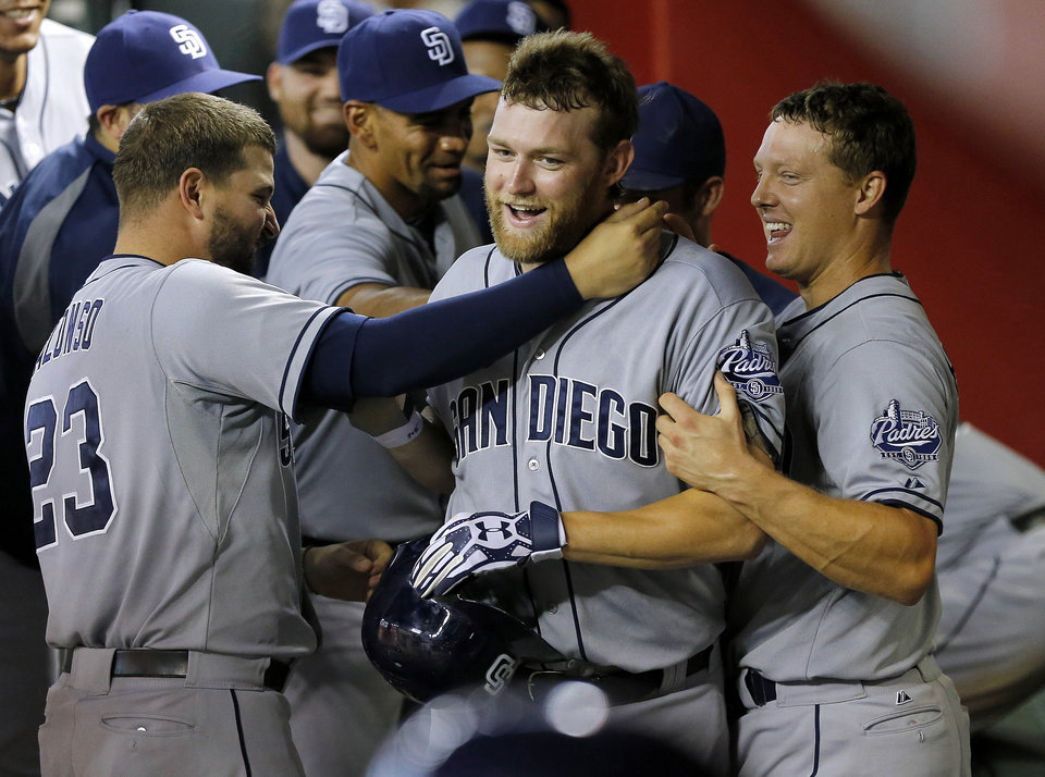 Photo - San Diego Padres players grab pitcher Andrew Cashner in the dugout, after first ignoring him, following his solo home run during the sixth inning of a baseball game against the Arizona Diamondbacks, Saturday, July 27, 2013, in Phoenix. (AP Photo/Matt York)