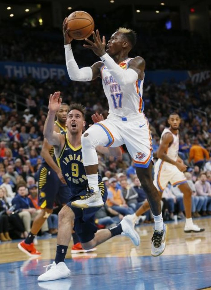 Photo -  Oklahoma City's Dennis Schroder, right, takes the ball to the basket in front of Indiana's T.J. McConnell during Wednesday night's game  at Chesapeake Energy Arena. [Nate Billings/The Oklahoman]