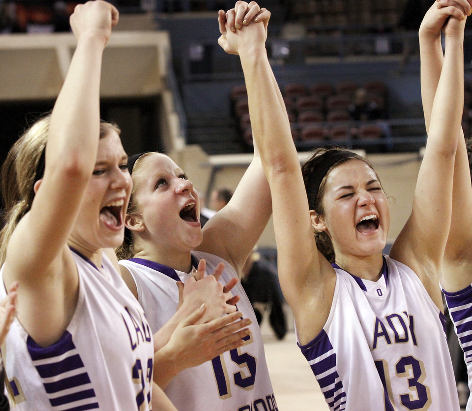 Photo - From left, Kenadey Grellner, Madi Grellner and Rae Grellner raise their arms and scream as the Lay Warriors are proclaimed the state champions after their win over Red Oak in the  Class B girls high school basketball championship game in the Jim Norick Arena at State Fair Park on  Saturday, March 8, 2014.   Okarche defeated Red Oak, 66-41. Photo by Jim Beckel, The Oklahoman