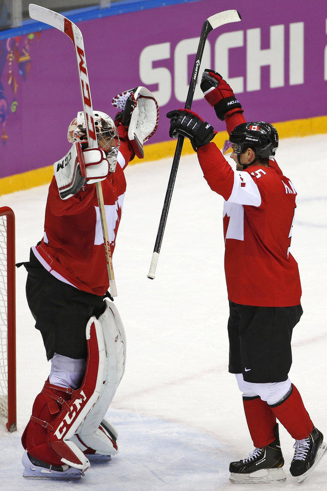 Photo - Goalkeeper Carey Price of Canada (31) and Dan Hamhuis of Canada (5) celebrate their 3-0 win over Sweden in the men's gold medal ice hockey game at the 2014 Winter Olympics, Sunday, Feb. 23, 2014, in Sochi, Russia. (AP Photo/Petr David Josek)