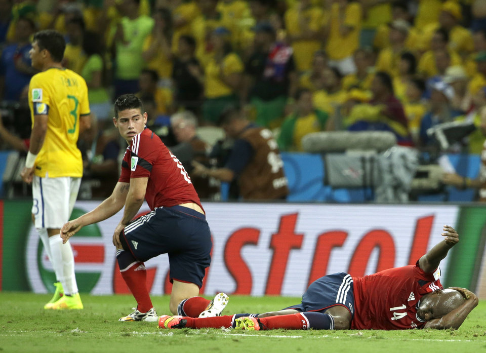 Photo - Colombia's Victor Ibarbo grimaces after being hit in the head as Colombia's James Rodriguez looks on during the World Cup quarterfinal soccer match between Brazil and Colombia at the Arena Castelao in Fortaleza, Brazil, Friday, July 4, 2014. (AP Photo/Hassan Ammar)