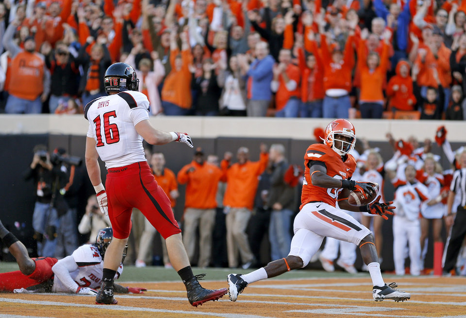 Photo - Oklahoma State's Isaiah Anderson (82) scores a touchdown in front of Texas Tech's Bruce Jones (24) and Cody Davis (16) during a college football game between Oklahoma State University (OSU) and Texas Tech University (TTU) at Boone Pickens Stadium in Stillwater, Okla., Saturday, Nov. 17, 2012.  Photo by Bryan Terry, The Oklahoman