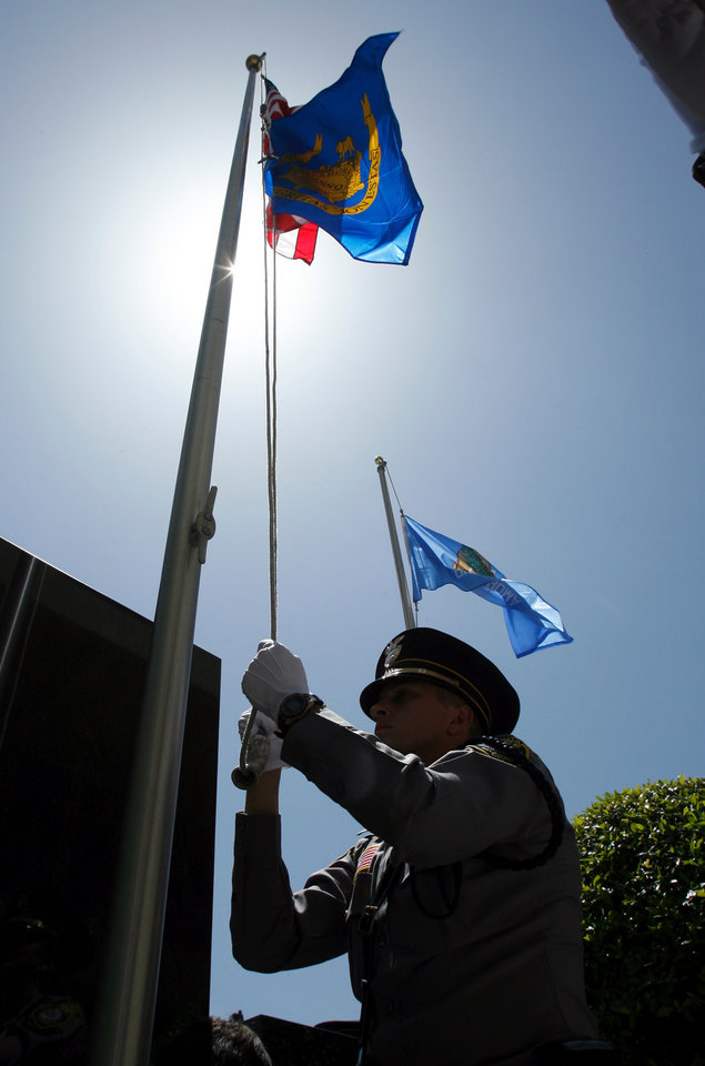 Photo - The honor guard raises the flag during a ceremony remembering fallen officers at a memorial in front of Oklahoma City Police Headquarters in Oklahoma City, Oklahoma on Friday, May 9, 2008.   BY STEVE SISNEY, THE OKLAHOMAN