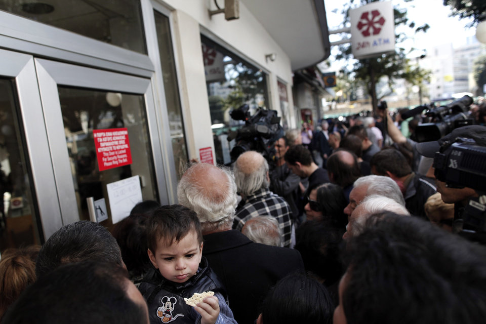 Photo - People wait outside a branch of Laiki Bank in Nicosia, Thursday, March 28, 2013. Banks in Cyprus reopened to customers for the first time in nearly two weeks Thursday, albeit with strict restrictions on transactions, after being closed to prevent people withdrawing all their savings during the country's acute financial crisis. Large lines had formed outside the banks ahead of the opening of banks for six hours from noon. (AP Photo/Petros Giannakouris)