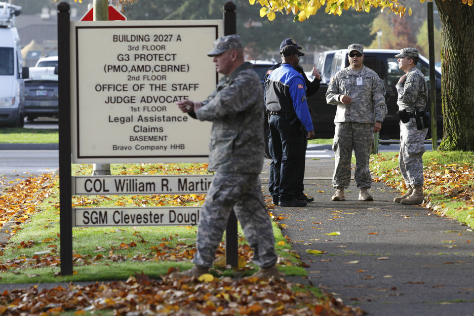 Photo -   Soldiers and security officers stand Monday, Nov. 5, 2012, outside the building housing a military courtroom on Joint Base Lewis McChord in Washington state, where a preliminary hearing began Monday for U.S. Army Staff Sgt. Robert Bales. Bales is accused of 16 counts of premeditated murder and six counts of attempted murder for a pre-dawn attack on two villages in Kandahar Province in Afghanistan last March. (AP Photo/Ted S. Warren)