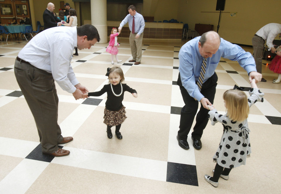 Chris Carrol and his 2 year old daughter Maggie, left, and Mike Sheline and his three year old daughter Brooke dance during the Deer Creek Daddy daughter dance at Deer Creek High School in Oklahoma City, OK, Saturday, January 26, 2013,  By Paul Hellstern, The Oklahoman