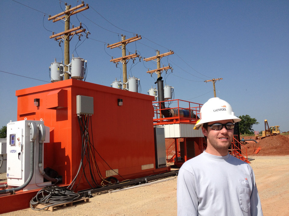 Jarod Tracy, production engineer for Devon Energy Corp., stands in front of a prototype General Electric generator southwest of Stillwater. The generator runs on natural gas in a part of northern Oklahoma\'s Mississippian oil play where utility power is not available. - provided