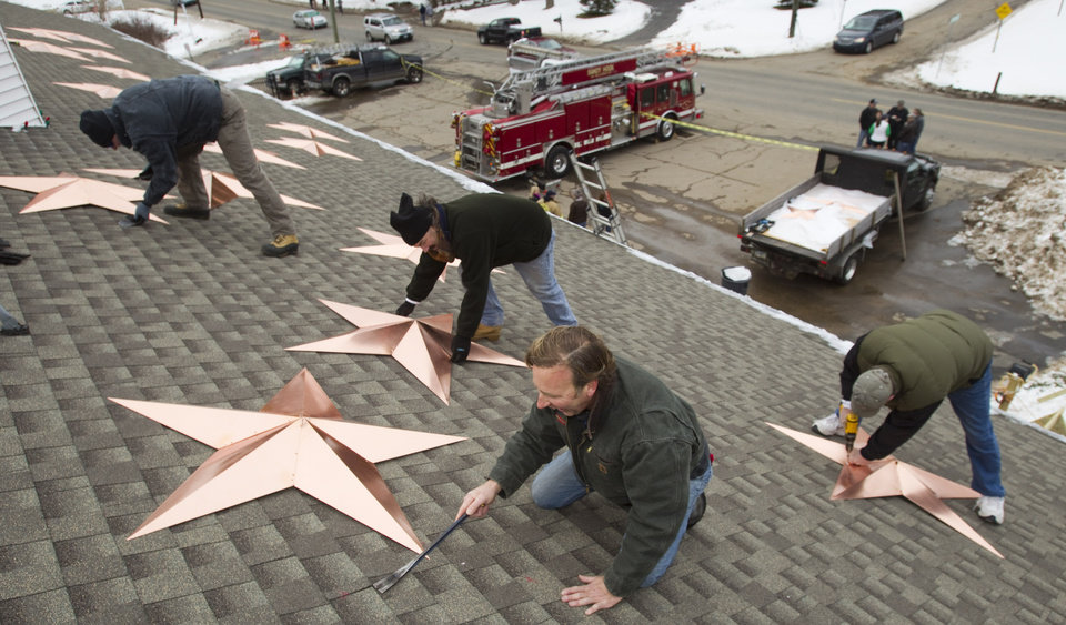 Photo - Volunteers, from left, Adrian Szepietowski, Guy Veneruso, Craig Schultz and Len Sabia, work on the installation of 26 stars on the roof of the Sandy Hook fire station Tuesday, Jan. 1, 2013, in Newtown, Conn. The stars were made and installed by a group of local contractors to honor the memory of the victims of the Sandy Hook school shooting. Nearly three weeks after the shooting rampage, classes are set to begin again for the Sandy Hook students Thursday, Jan. 3, 2013 at a repurposed school in the neighboring town of Monroe. (AP Photo/The News-Times, Brett Coomer)