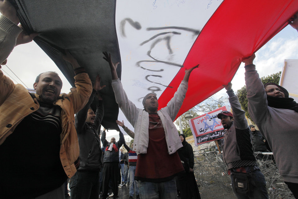 Photo - Egyptian protesters shout anti-Mohammed Morsi slogans under a giant flag in front of the presidential palace in Cairo, Egypt, Friday, Feb. 1, 2013. Arabic banner reads,