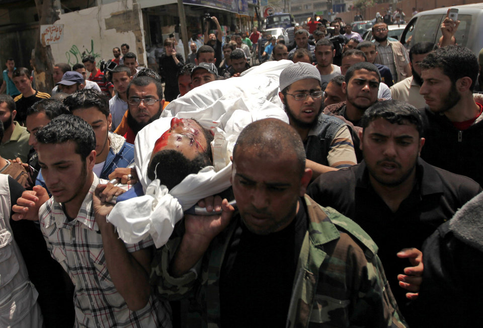 Photo - Palestinians carry the body of Haitham Mishal, 29, during his funeral at the Shati refugee camp in Gaza City, Tuesday, April 30, 2013. An Israeli aircraft attacked a motorcyclist in Gaza on Tuesday, killing the rider and wounding several other people in the first deadly airstrike in the Palestinian territory since a truce was reached with Palestinian militants last November. The Israeli military said the airstrike killed Haitham Mishal, whom it identified as a militant involved in the April 17 rocket attack on the southern Israeli resort town of Eilat. (AP Photo/Hatem Moussa)