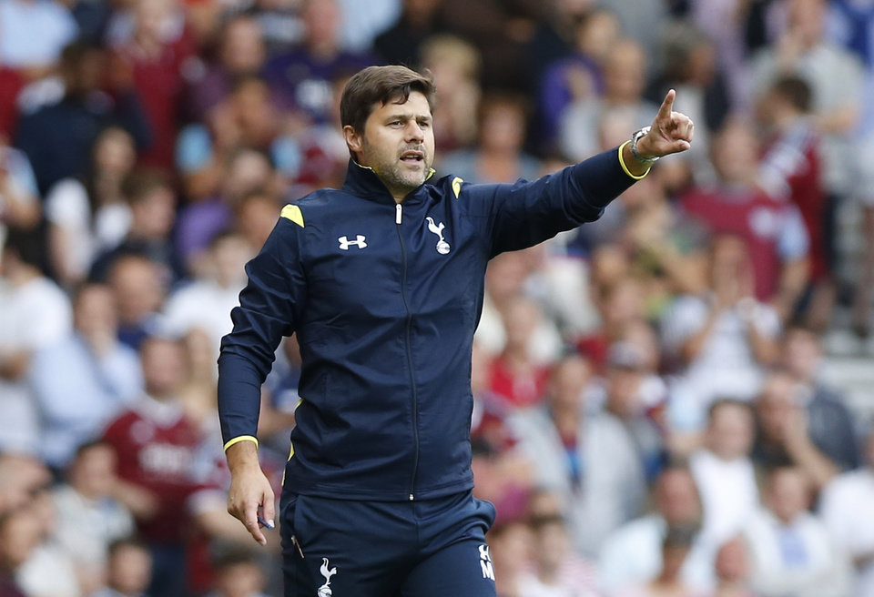 Photo - Tottenham Hotspur's manager Mauricio Pochettino gestures to his players as he watches his team play against West Ham United during their English Premier League soccer match at Upton Park, London, Saturday, Aug. 16, 2014. (AP Photo/Sang Tan)