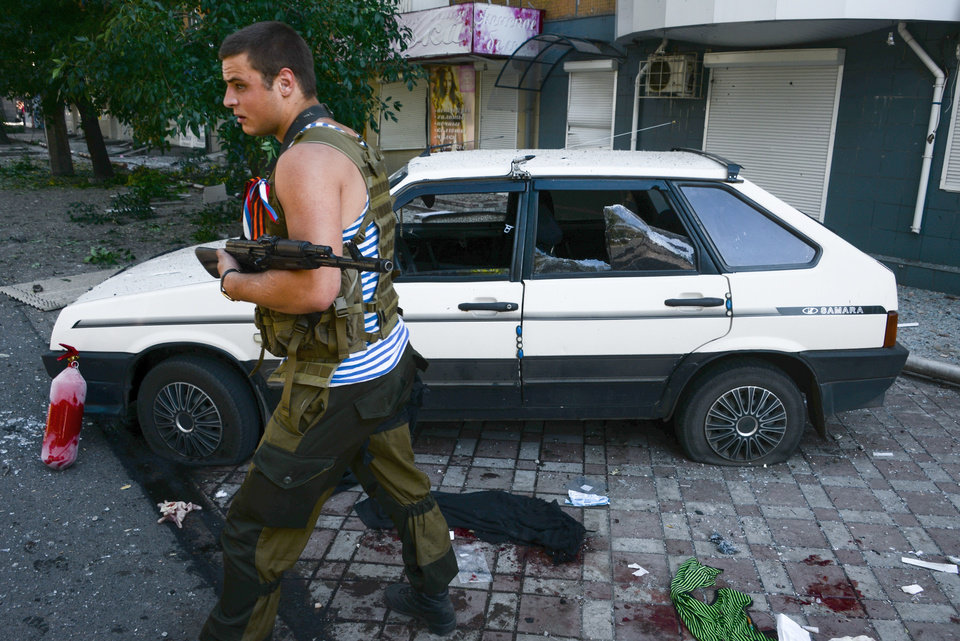 Photo - A Pro-Russian rebel passes by a car which was hit by shrapnel from a shell after shelling in the town of Donetsk, eastern Ukraine, Wednesday, Aug. 27, 2014. The Obama administration accused Russia on Wednesday of orchestrating a new military campaign in Ukraine, helping rebel forces expand their fight in the country's east and sending tanks, rocket launchers and armored vehicles toward communities elsewhere. (AP Photo / Mstislav Chernov)