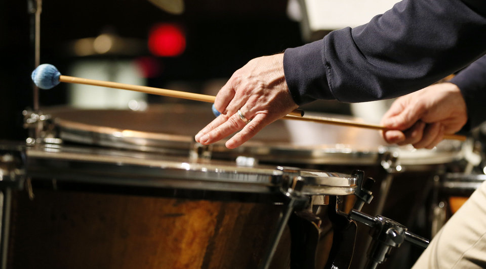 Lance Drege dampens a timpani head during a rehearsal of Christopher Rouse\'s