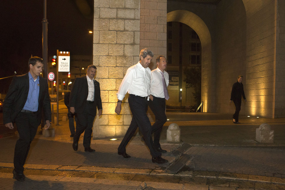 Photo - Escorted by security, U.S. Secretary of State John Kerry, center, walks with Frank Lowenstein, senior advisor to the secretary on Middle East issues, as they return to their hotel just after 4 a.m. on Sunday, June 30, 2013 after finishing a meeting with Israeli Prime Minister Netanyahu that took over six hours. After the marathon meeting, Kerry decided to get some air by walking to a park near the hotel where he is staying and the meeting was held. Kerry is shuttling between Palestinian and Israeli leaders in hopes of restarting peace talks. (AP Photo/Jacquelyn Martin, Pool)