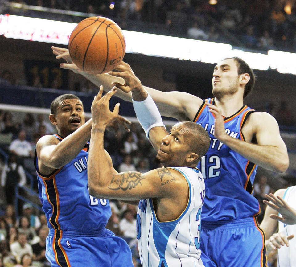 Photo - Oklahoma City guard Earl Watson, left, and center Nenad Krstic reach for a loose ball over New Orleans forward David West during the Hornets' 108-90 win Saturday. Ap photo