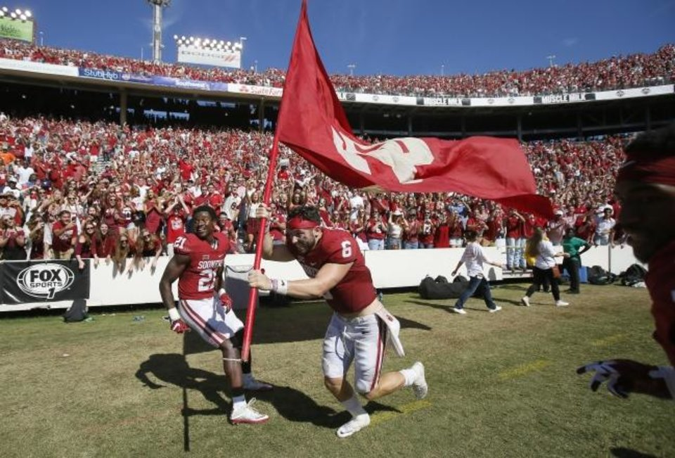 Photo -  Baker Mayfield (6) celebrates with an OU flag after beating Texas 45-40 in the Red River Showdown on Oct. 8, 2016. [Bryan Terry/The Oklahoman]