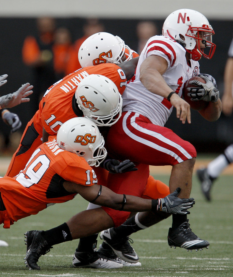 Photo - Nebraska's Roy Helu Jr. gets away from OSU's Johnny Thomas, top, Markelle Martin, and Brodrick Brown during the college football game between the Oklahoma State Cowboys (OSU) and the Nebraska Huskers (NU) at Boone Pickens Stadium in Stillwater, Okla., Saturday, Oct. 23, 2010. Photo by Bryan Terry, The Oklahoman