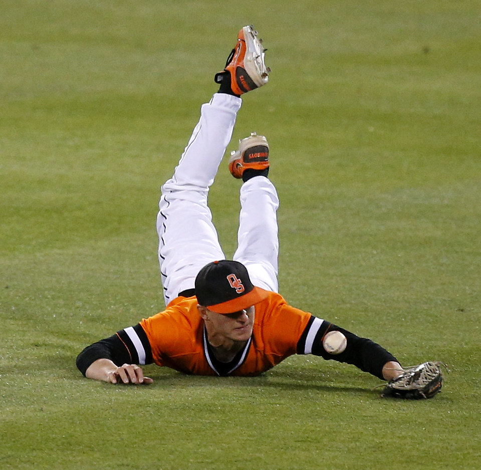 Photo - OSU's Corey Hassel is unable to make the catch but was able to throw to second for the out in the 16th inning of a Bedlam baseball game between Oklahoma State University and the University of Oklahoma in Stillwater, Tuesday, April 15, 2014. Photo by Bryan Terry, The Oklahoman