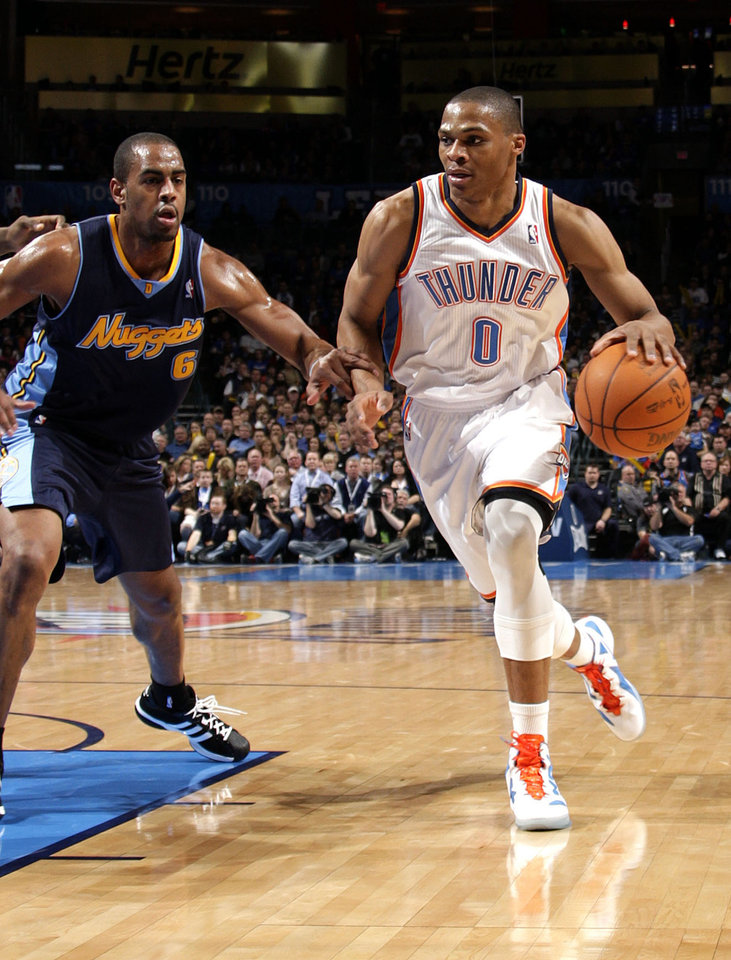 Photo - Oklahoma City's Russell Westbrook (0)drives to the basket past Denver's Arron Afflalo (6) during the NBA basketball game between the Oklahoma City Thunder and the Denver Nuggets at the Chesapeake Energy Arena, Sunday, Feb. 19, 2012. Photo by Sarah Phipps, The Oklahoman