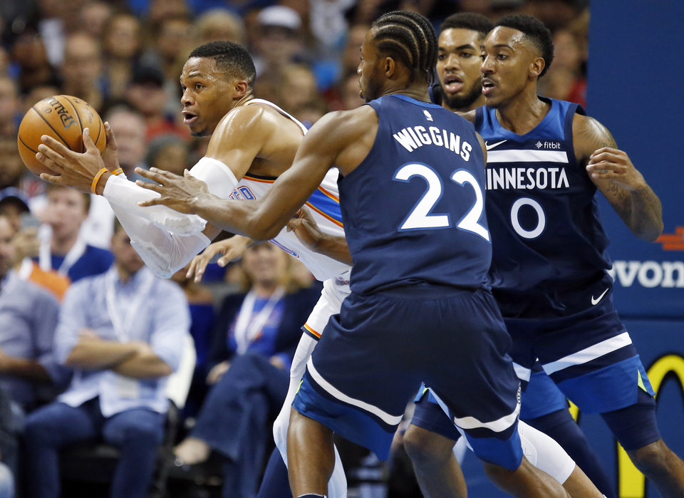 Photo - Oklahoma City's Russell Westbrook (0) passes away from Minnesota's Andrew Wiggins (22), Karl-Anthony Towns (32) and Jeff Teague (0) during an NBA basketball game between the Oklahoma City Thunder and the Minnesota Timberwolves at Chesapeake Energy Arena in Oklahoma City, Sunday, Oct. 22, 2017. Minnesota won 115-113. Photo by Nate Billings, The Oklahoman